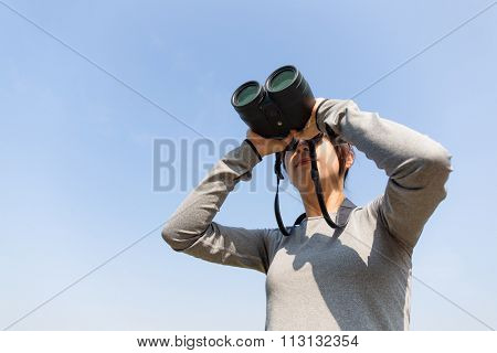 Asian woman looking though binoculars with clear blue sky