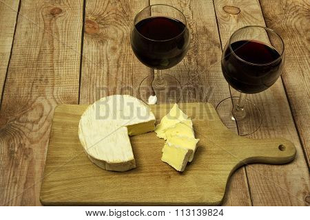 Two Wine Glasses With Red Wine,bottle Of Wine And Cheese On Wood