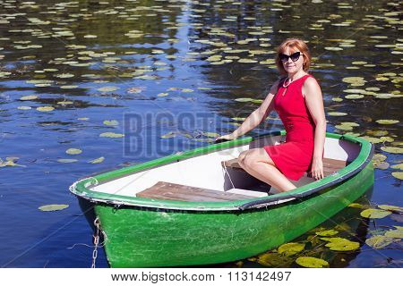 Lady in red dress sitting in boat
