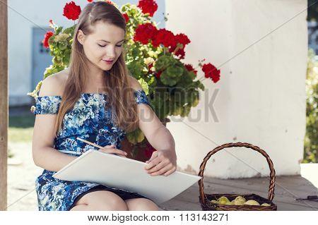 Lovely romantic girl drawing in the album
