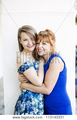 Cheerful mother and daughter holding together sweetly