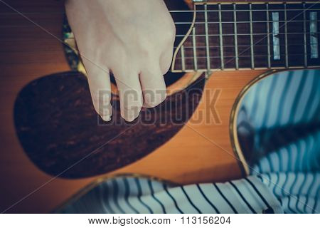 vintage style close-up of female hands playing guitar