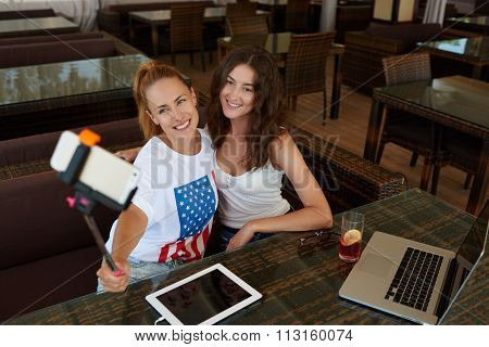 Cheerful women making photo on cell telephone camera via self stick during brunch in cafe