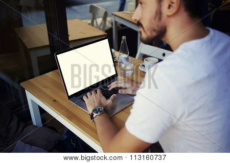Cropped image of man learning on-line via laptop computer during lunch in cafe