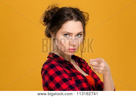 Close up portrait of angry irritated young woman in plaid shirt pointing on you over yellow background