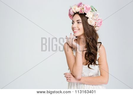 Portrait of attractive cheerful young woman in white dress and flower wreath looking away over white background