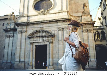 Back view of a young woman traveler with a backpack on her shoulder out sightseeing in city