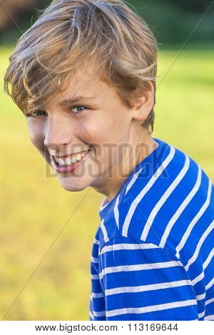 Young happy laughing male boy teenager blond child outside in summer sunshine wearing a blue striped t-shirt