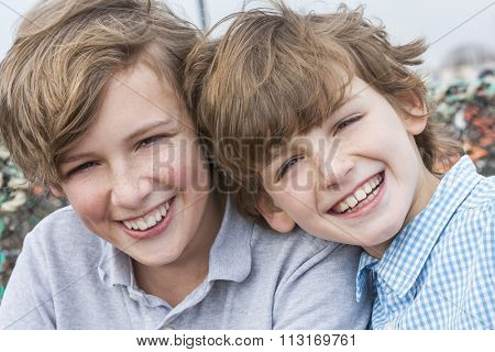 Outdoor portrait photograph of young happy boy children brothers smiling together