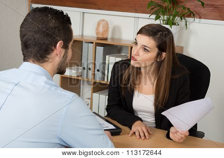 Woman And Man At The Office Desk. Woman Explains Something