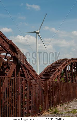New wind turbine and old rusty bridge