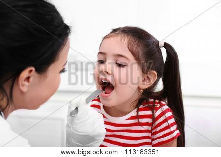 Doctor examining child's throat