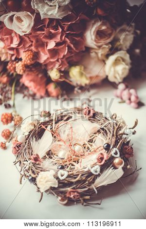 Engagement rings on nest-styled pillow in front of bridal bouquet with red and burgundy flowers on w