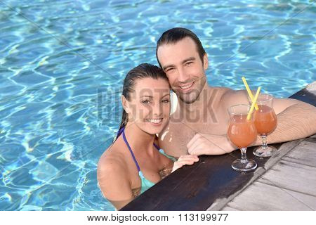 Couple drinking cocktail in swimming pool