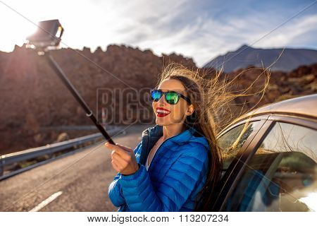 Woman making selfie portrait near the car