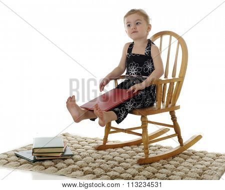 A beautiful preschooler looking satisfied in her rocker, with a book in her lap and a stack of others by her feet.  On a white background.