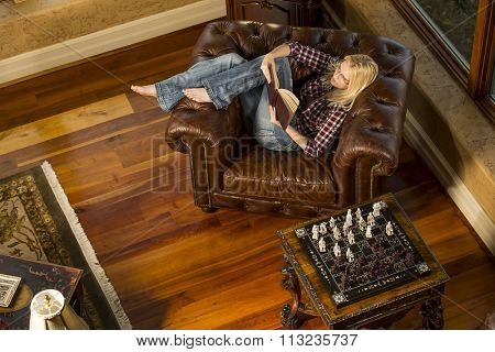 A blonde female model reading a book in a home environment