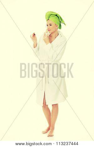 Woman in towel turban smelling parfume.