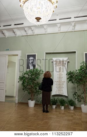 ST. PETERSBURG, RUSSIA - DECEMBER 7, 2015: Woman reading the list of great composers performing in the Great Philharmonic Hall. This day the list was re-opened after restoration