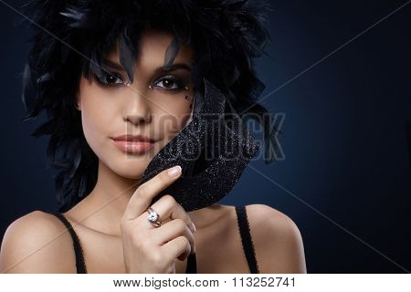Carnival portrait of smiling beauty with elegant glittering mask and black feather boa.