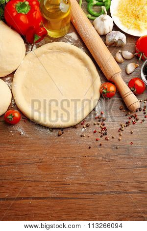 Dough basis and ingredients for pizza, on the table