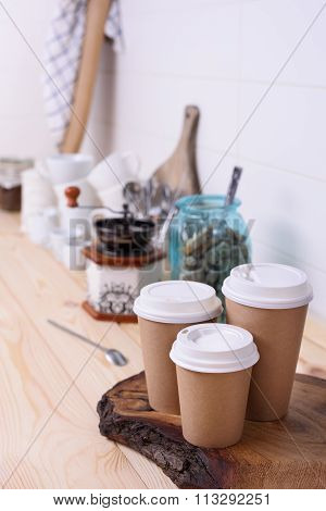 Coffee cups for take away, various sizes, and kitchenware on wooden lunch counter.