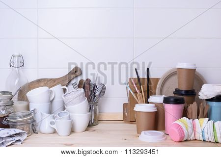 Various types of drink ware, ceramic and paper, on wooden lunch counter, white background.