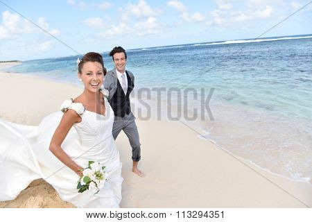 Just married couple running on a caribbean beach