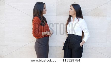 Two chic relaxed young women standing chatting together in front of a white exterior wall with bilateral copyspace  three quarter pose