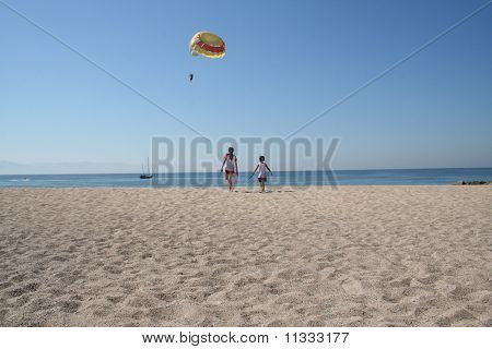 Two children walk towards the water while a parasailer flys nearby at a sandy beach near Puerto Vallarta, Mexico. poster