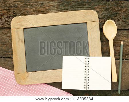 The slate chalkboard and wooden spoon and blank earth tone note book with pencil