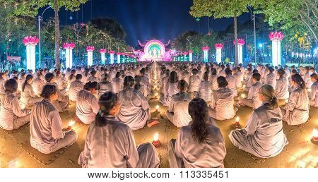 Buddhist sitting hands in prayer in candlelit