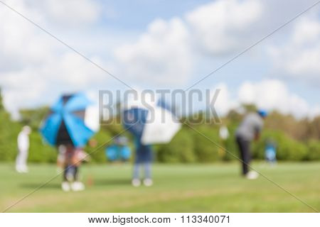 Blurred Photo Of Golfer And Caddy In Green Golf Course.
