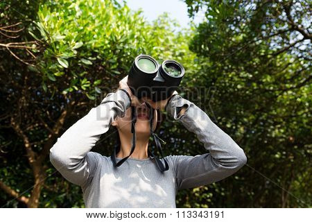 Asian Young woman looking though binocular in forest