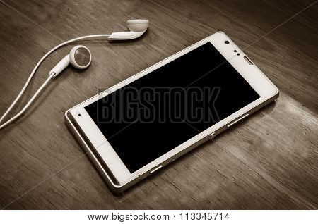 beautiful earplugs and smartphone on wood surface with color filters vintage
