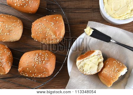 High angle view of sesame dinner rolls on a wire rack, with bread plate, and butter crock and knife.