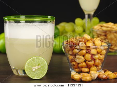 The Peruvian cocktail Pisco Sour with the Peruvian snack roasted corn called cancha and grapes limes Pisco Sour and habas (Peruvian roasted beans) in the background (Selective Focus on the front) poster