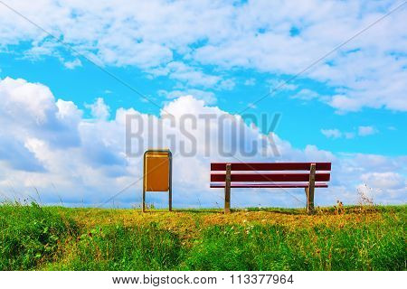 bench and dustbin on an embankment with vista to the sea and sky