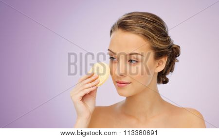 young woman cleaning face with exfoliating sponge