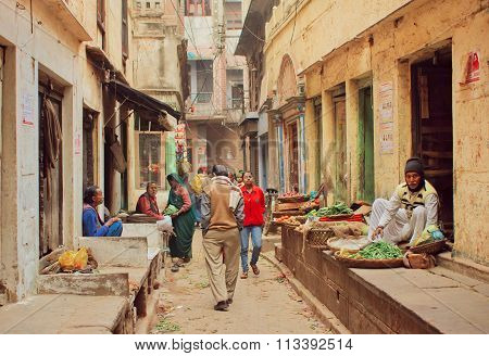 Crowd Of People Walking On Narrow Street With Food Sellers And Small Vegetable Stores