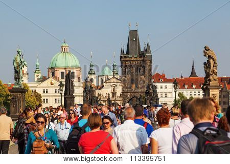 PRAGUE, CZECHIA - SEPTEMBER 04: crowd of unidentified people walking on the Charles Bridge on September 04, 2014 in Prague. The centre of Prague is protected by UNESCO and a famous travel destination
