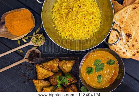 Indian Pilau Rice In Balti Dish Served With Chicken Tikka Masala Curry And Side Dishes