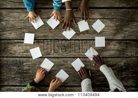 Four Children Of Mixed Races Assembling A Heart Shape Of White Cards
