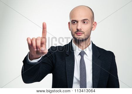 Concentrated handsome young businessman in formalwear  touching copyspace with finger over white background