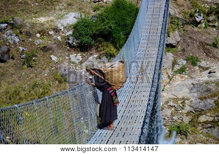 Nepalese woman on a bridge