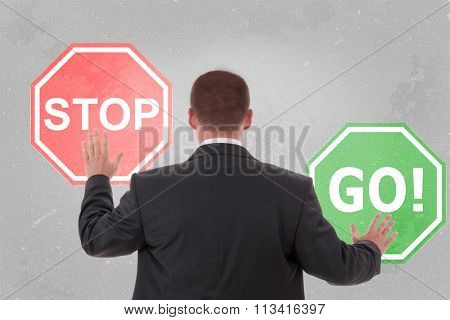 Businessman standing and holding a stop sign and go sign