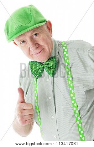 A senior Irishman in a green hat, suspenders and sparkly bowtie giving a happy thumbs up.  On a white background.