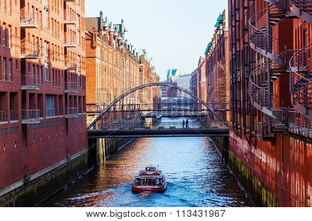 HAMBURG, GERMANY - MARCH 09: excursion boat with unidentified people in the Speicherstadt on March 09, 2014 in Hamburg. It is the largest timber pile founded warehouse district in the world.