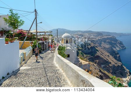 Old traditional narrow stone made street promenade to Thira town on cliff of Santorini island.