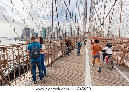 New York City,  USA  - October 08, 2015: Brooklyn Bridge with unidentified people in NYC. Its one of the oldest bridges of either type in the US and an icon of NYC as well as a National Historic Landmark